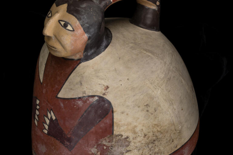 Image of a pottery bottle; single tapered spout with strap handle to modeled and painted human head; round bottom;