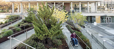Wheelchair traveling on path of Lower Sproul stairway ramp.